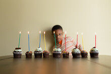 Boy Behind Row Of Cupcakes With Lit Candles