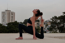 Thin Athletic Woman Stretching In A Yoga Pose. Shot In An Empty Urban Park With Tel Aviv Buildings In The Far Background.