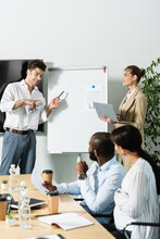 Smiling Businessman With Newspaper Pointing At Flip Chart Near Multiethnic Colleagues