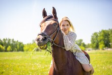 A Young Rider Woman Blonde With Long Hair In A Dress Posing With Brown Horse On A Field And Forest Background, Russia