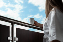 Young Woman Hold Cup Of Coffee Or Tea On The Hotel Balcony In The White Bathrobe Besides Bright Blue Sky. Lady On Vacation Or Business Trip.