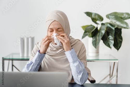 Fotografiet Arabian muslim mature businesswoman in hijab sneezing at home office