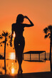 Leinwandbild Motiv Full length vertical view silhouette slim young sexy woman wear bikini pose alone near swimming pool, tropical trees, calm sea and glowing sun on background. Summer holidays, vacation, resort concept
