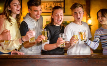 Group Of Millennials Happy Friends Drinking And Toasting Beer In Scottish Pub - Young Teenagers Having Fun Together In A Bar Restaurant - Concept About Teenagers In Happy Hour Celebration Time.