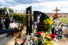 A Catkin Standing In Front Of A Grave In A Christian Cemetery, Blurry Tombstones And Artificial Flowers In The Background.