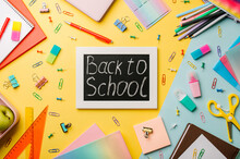 Blackboard With Letters Back To School Made With Chalk And Stationery, School Supplies On Yellow And Blue Background. Top View Or Flat Lay. Back To School Concept