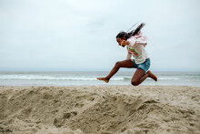 Preteen Black Girl Jumping Into Sand At Beach