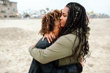 Mom Tenderly Hugging Teen Son At Beach
