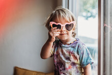 Young Toddler Boy In Colorful Sunglasses And Tie Dye Shirt.