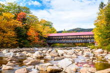 Historic Covered Bridge Spanning A Mountain River Running Through A Colourful Forest At The Peak Of Fall Foliage On A Partly Cloudy Autumn Day. Stunning Autumn Colours.