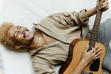 Young Man Laying Playing Guitar Smiling