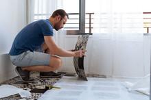 Man Preparing Floor Stickers During Renovation