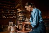 Focused brunette female artisan modeling ceramic tableware in pottery workshop