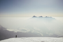 Man Taking Pictures At Mountain Peak In The Mist