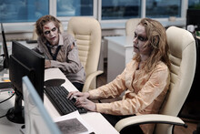 Gloomy Businesswoman With Zombie Greesepaint Using Computer By Desk