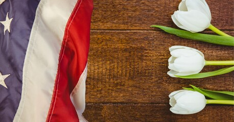 American flag and white tulip flowers on wooden background