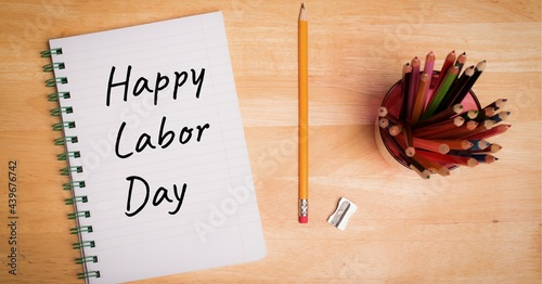 Happy labor day text on dairy and pencil stand on wooden surface
