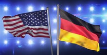Composition Of Billowing American Flag And German Flag Against Wall Of Spotlights