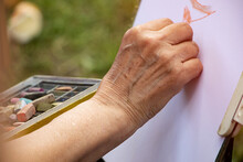 Street Artist Holding A Box With Multicolored Crayons And Pencils For Drawing.Close Up Photography Of Hands And Drawing Supplies.He Drawing Behind The Easel With White Paper.