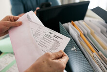 Taxes: Woman Opens Envelope With 1099 Miscellaneous Income Form