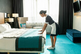 Pretty chambermaid bending over done bed in hotel room
