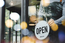 Hand Of Asain Staff Woman Wearing Apron Turning Open Sign Board On Glass Door In Modern Cafe Coffee Shop, Hotel Service, Cafe Restaurant, Retail Store, Small Business Owner, Food And Drink Concept