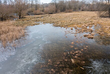 Frozen Floodplain From Drone Perspective In Winter. Nature Scenery With Water On A Meadow With Dry Grass From Above. Untouched Wilderness Near River.