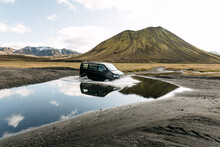 A Travel Van Crossing Through A Huge Puddle Of Water In Iceland.