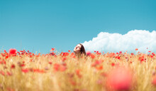 Girl Enjoying The Sun In A Poppies Field