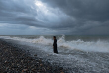 Woman In Black Dress Standing By The Sea At Dusk
