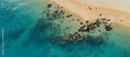 Fotografia Rocks on the shoreline and underwater in a sparkling blue ocean at low tide on a