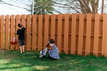Children Searching For Easter Eggs In The Backyard.