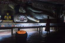 A Woman Admiring A Statue Of A Resting Buddha