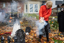 Boy Setting Up Skull Scary Halloween Decorations In Front Yard For Trick-Or-Treat Fright