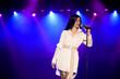 Leinwandbild Motiv Cool singer with microphone on bright backlit stage in bright blue lights