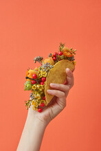 Woman Holding Taco With Flowers On Orange Background