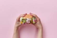 Woman Holding Burger With Roses On Pink Background