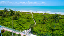 Beach In Sanibel Island, Florida With A Wooden Walkway Going Through Dense Vegetation To The Sand