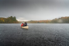 Father And Son Paddling Canoe In Heavy Rain Storm