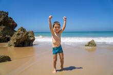 Kid With Raised Fists As A Sign Of Winner On A Spanish Beach