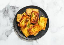 Plate Of Fried Tofu And Green Onion Garnish
