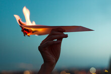 Female Hand Holding A Paper Plane On Fire