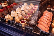 Fancy Baked Goods In A Dessert Case At A Bakery Including Pigs