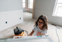 Girl Playing In The Living Room Of A New Home Build.