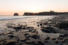 A Bright Orange Sun Sets Over The Ocean And A Rocky Seashore