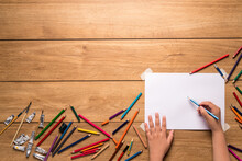 The Little Boy's Hand Is About To Draw And Around. There Are Many Different Wood Colors And Watercolor Painting Tools. Such As Paint Tubes And Paintbrushes Placed On A Wooden Table, With Copy Space.