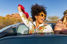 Black Girl Holding Red Feather Boa In Back Seat Of Convertible Car