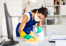 Female Cleaner Working In Protective Mask Productively On Task In Office
