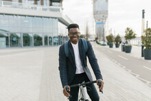Young African American Businessman Riding A Bicycle To Work In The Urban City Zone