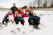 Kids Posing With Their Snowman